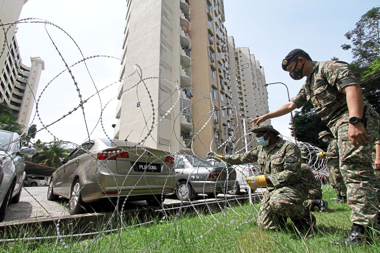 Army officers ensuring that the barbed wire temporary fencing is intact outside a block of flats in Paya Terubong, Penang, during the lockdown.