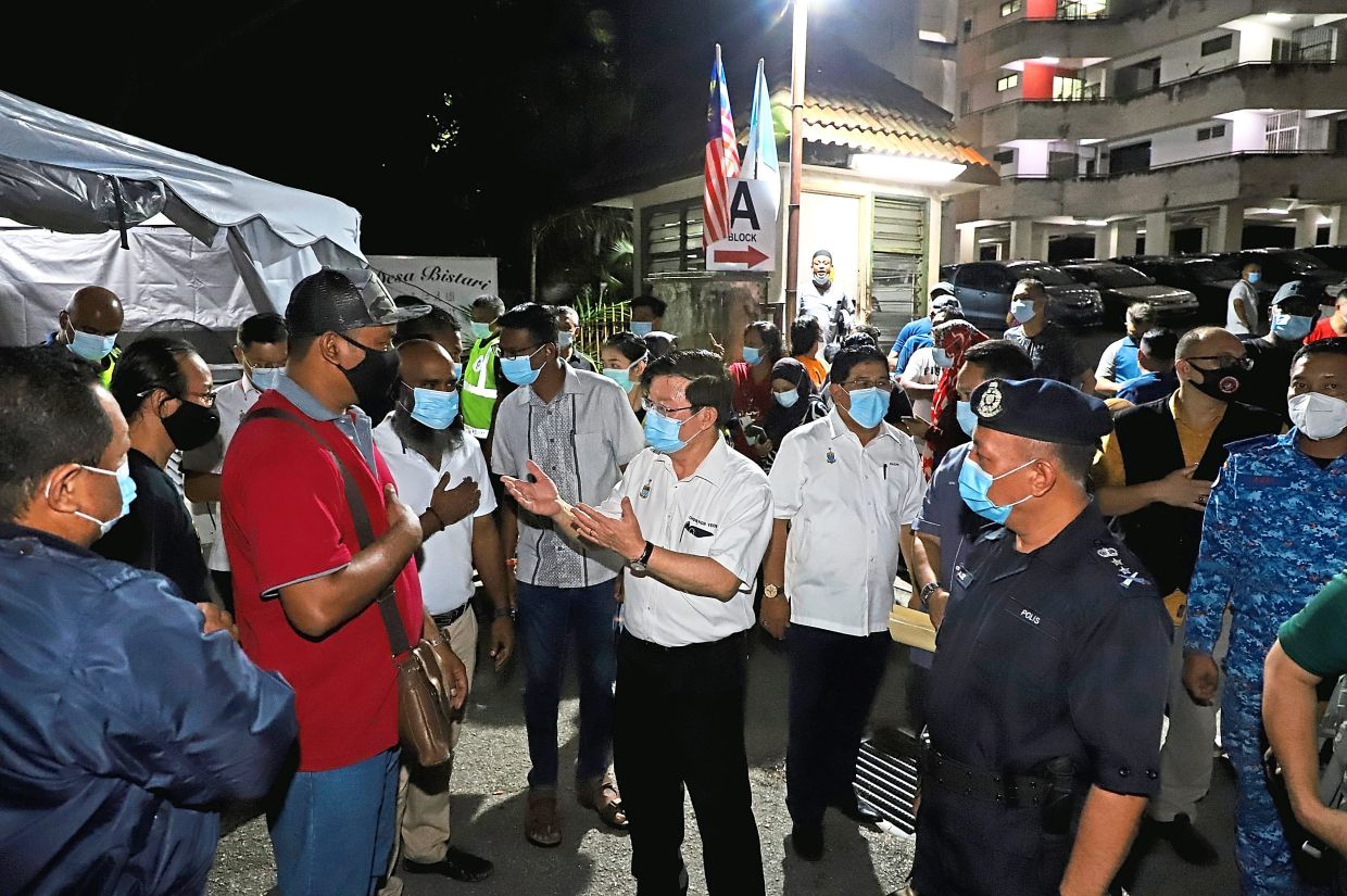 Chief Minister Chow Kon Yeow (middle) chatting with residents during a visit to Desa Bistari Apartments in Batu Uban before the lockdown there took effect at midnight on Sunday.