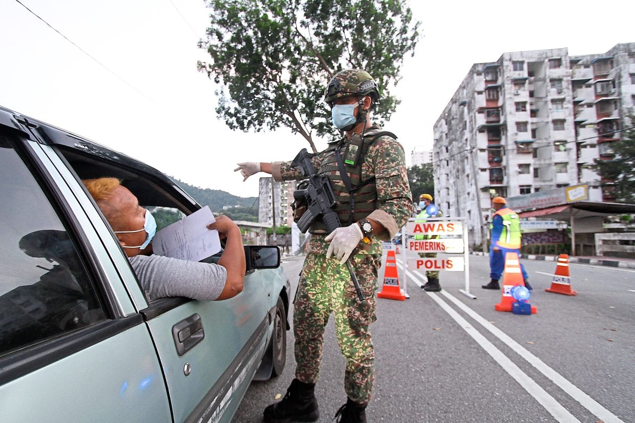 A motorist trying to get past a roadblock in the area. — Photos: CHAN BOON KAI and LIM BENG TATT/ The Star