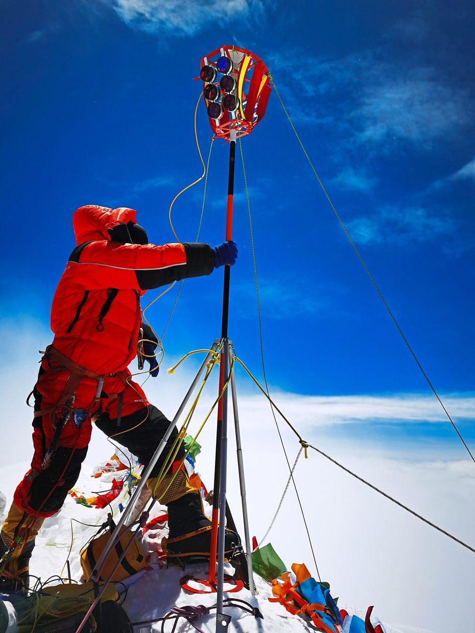 Peak research: A member of the Chinese survey team setting up equipment on the summit of Mount Everest, also known locally as Qomolangma. — AP
