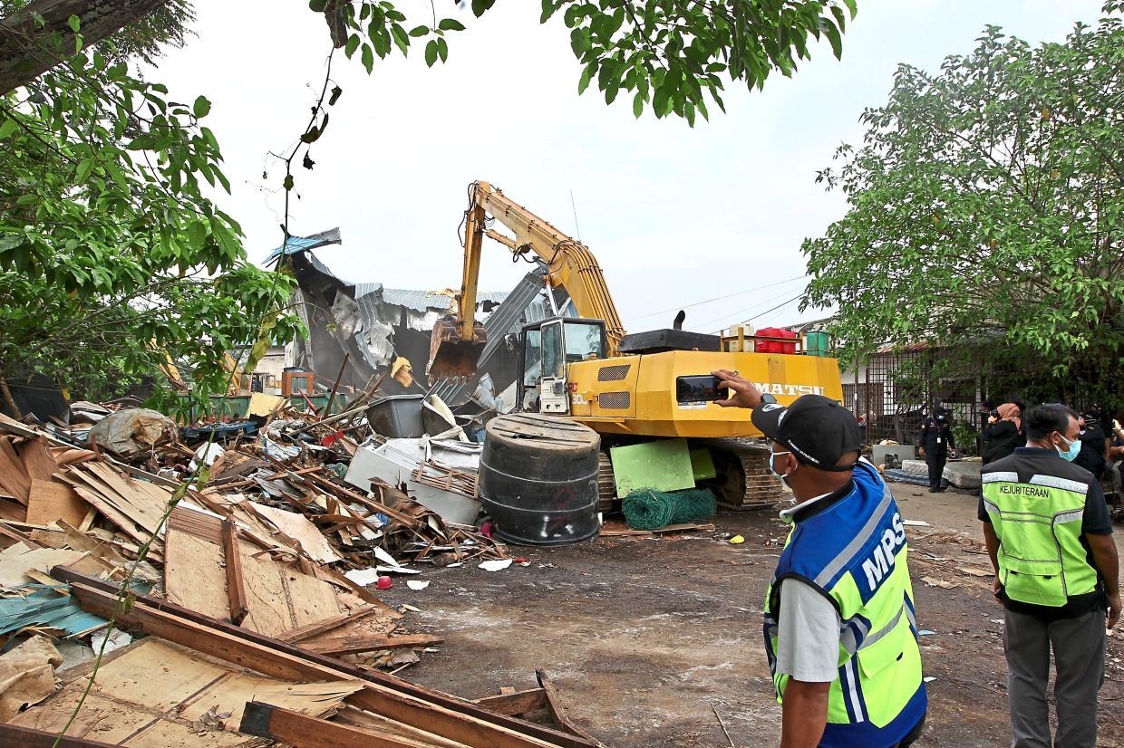 An excavator tearing down the illegal structures.
