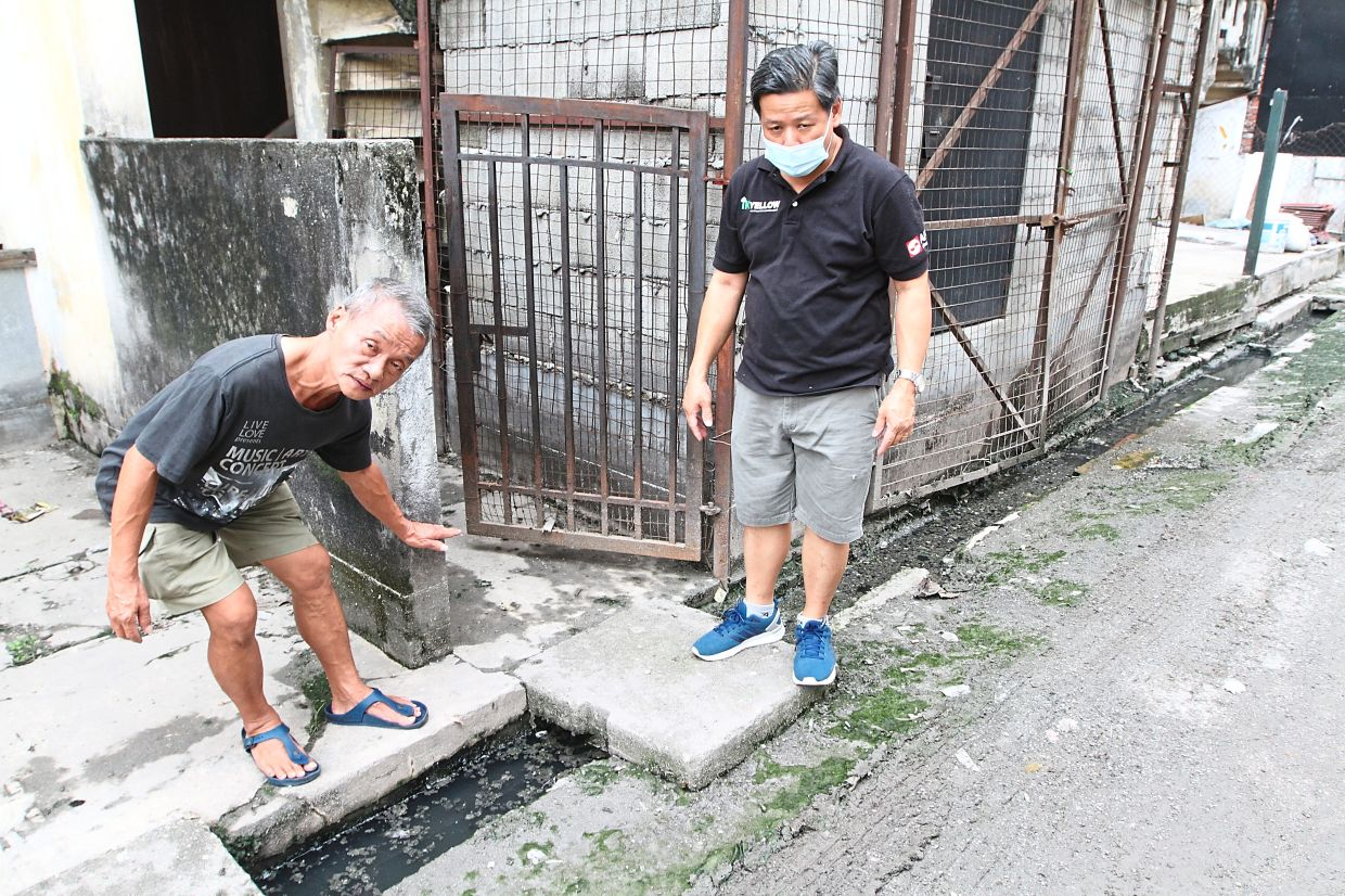 Ng (left) and Lim (right) showing the water level when it floods in Jalan Merak.