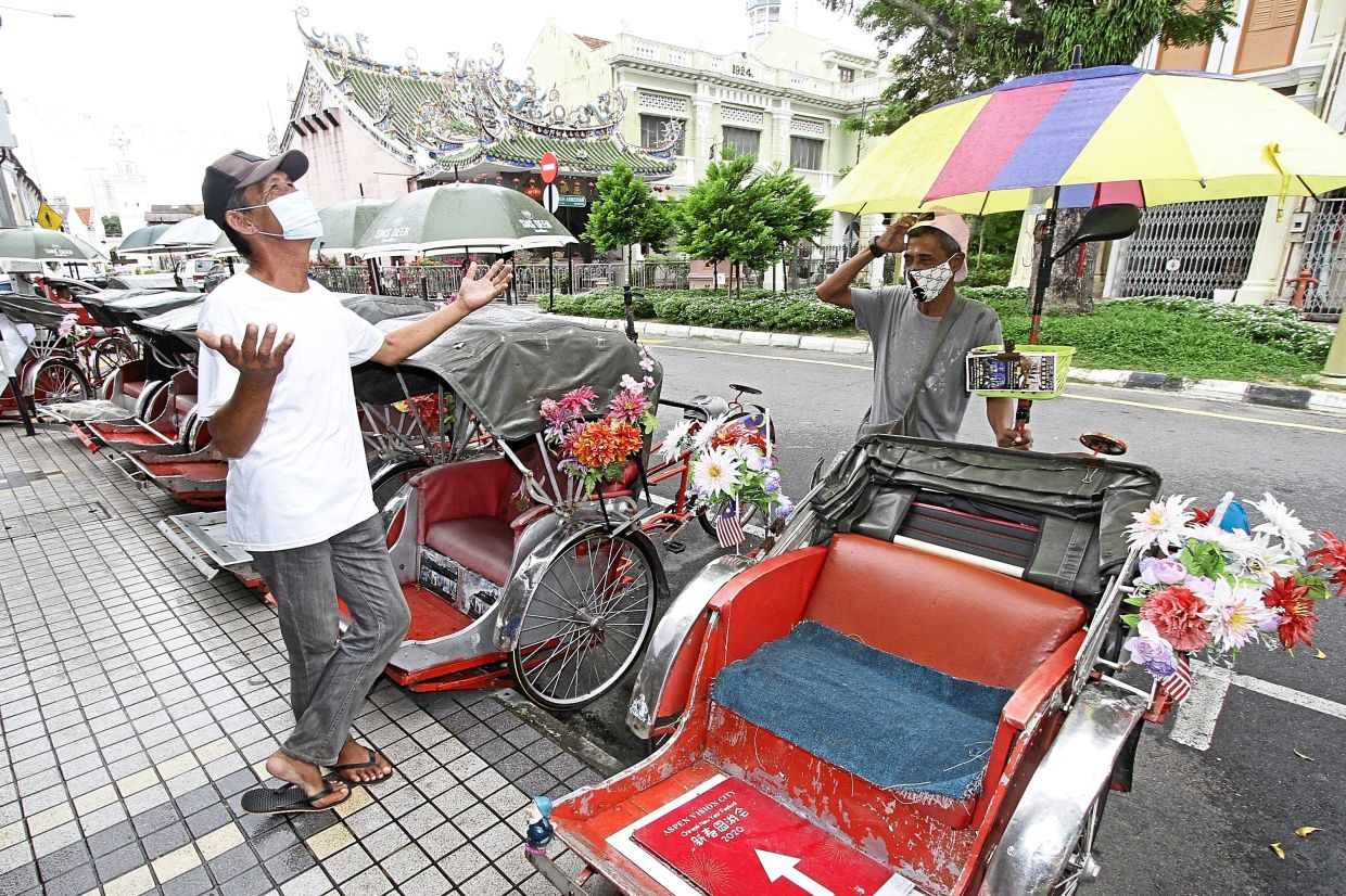 Both Shamsul (right) and Lau, have been sleeping in their trishaws as they can't earn enough to pay rent.