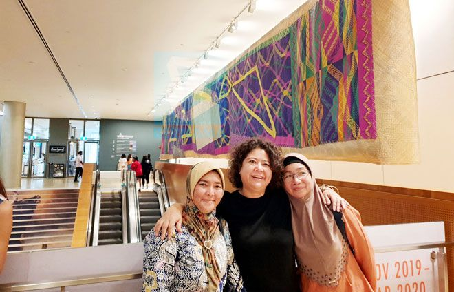 Sabah-based traditional weavers Roziah Jalalid (right) and Julitah Kulinting (left) with artist Yee I-Lann (centre) at the National Gallery Singapore. In the background is the 'Tikar-A-Gagah' installation. Photo: Bernama