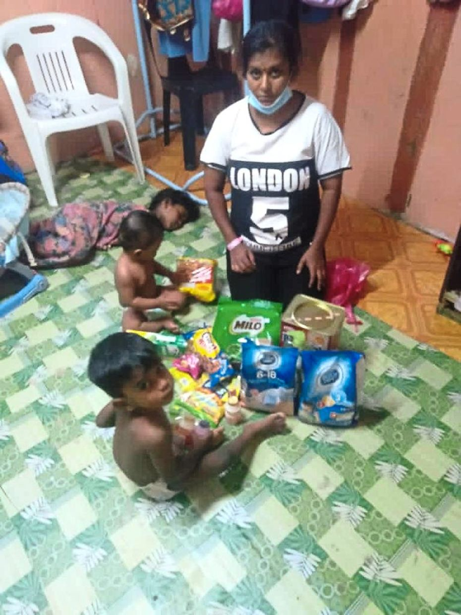 Kogilavani with their three children looking at the provisions donated to them by Penang Hindu Association at their rented room in Jalan Utama.