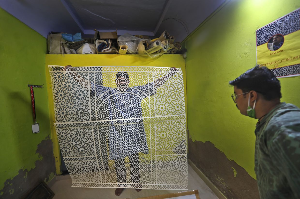Ram Soni, a paper cutting artist, shows his work at his home in Alwar some 160km from New Delhi, India. Photo: AP