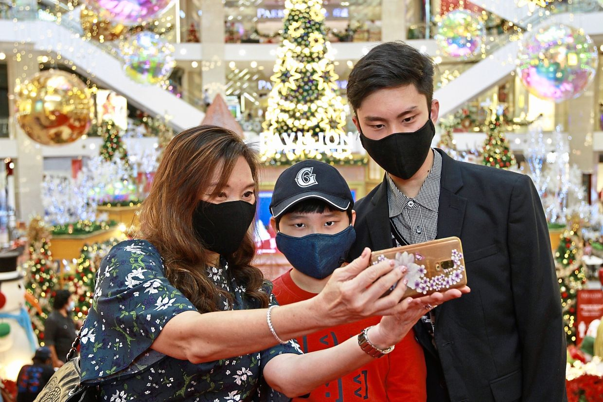 (from left) Homemaker Jessica Soo, 52, and her sons Justice Soo, 10 and Julius Soo, 15, capturing a happy moment amid the Christmas decorations in Pavilion Kuala Lumpur. - LOW LAY PHON/The Star