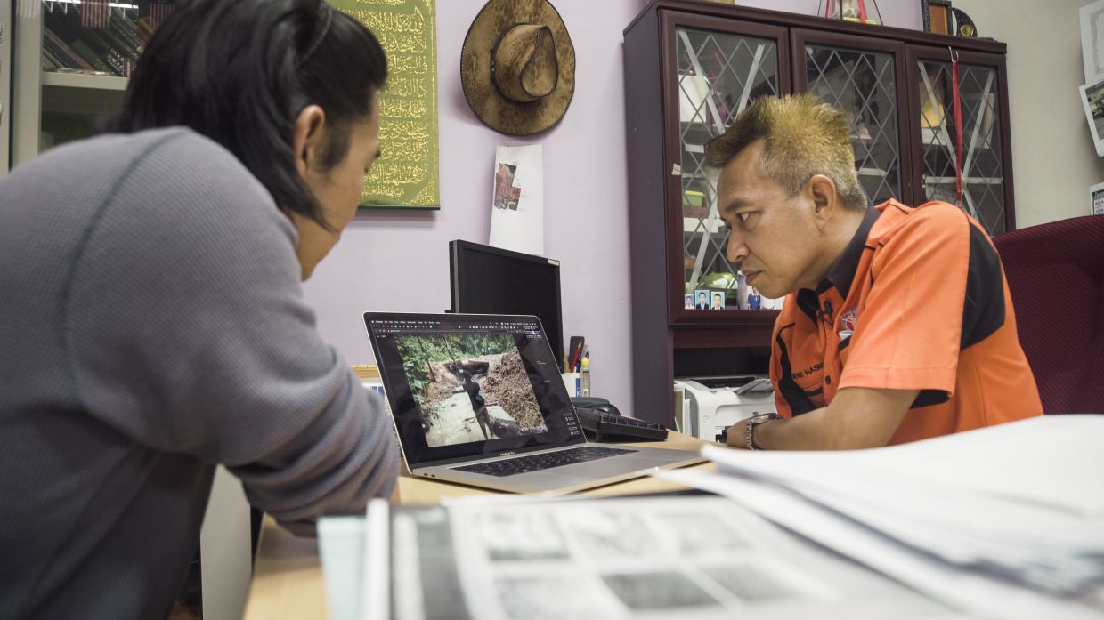 Prof Mohd Hasmadi Ismail (right) examines the evidence gathered by Orang Asli, that suggests logging activity in their ancestral land is damaging the environment, particularly the rivers. Photo by: Shanjeev Reddy