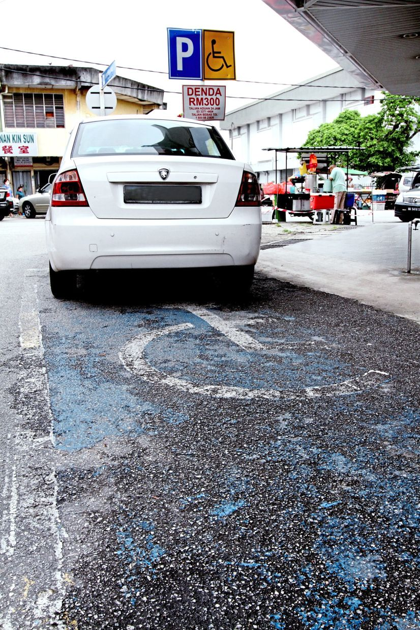 A car is partially parked at a space designated for people with disabilities at Jalan Menalu in Taman Chi Liung, Klang.