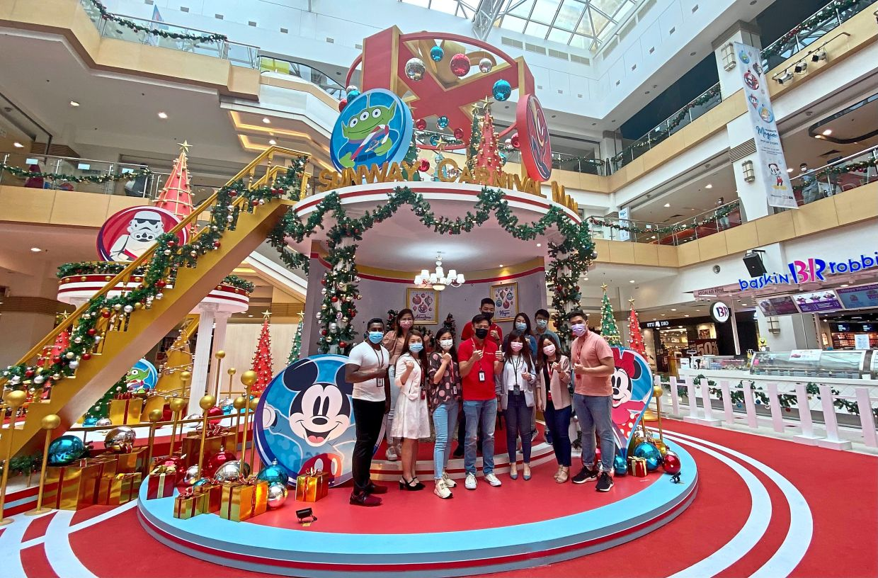 Chai (centre, in red) posing for a group photograph at the centre stage of the mall's Christmas decorations.— Photos: ZAINUDIN AHAD/The Star