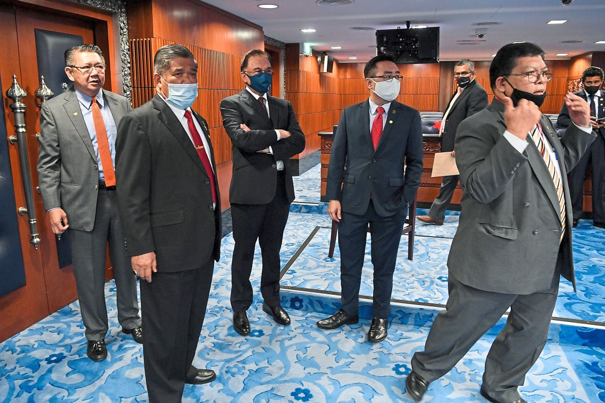 Not in favour: Anwar (third from right) and other opposition members preparing to walk out of the Dewan Rakyat due to the presence of the three MPs who were supposed to be quarantining at home. — Bernama
