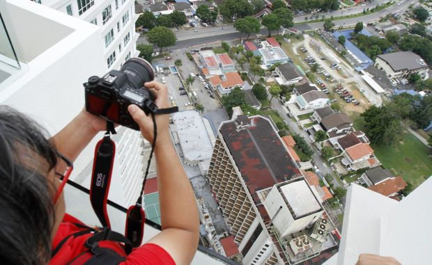 A photographer on the 40th floor of The Cove condominiums block with the 20-storey Copthorne Orchid Hotel below. - Filepic