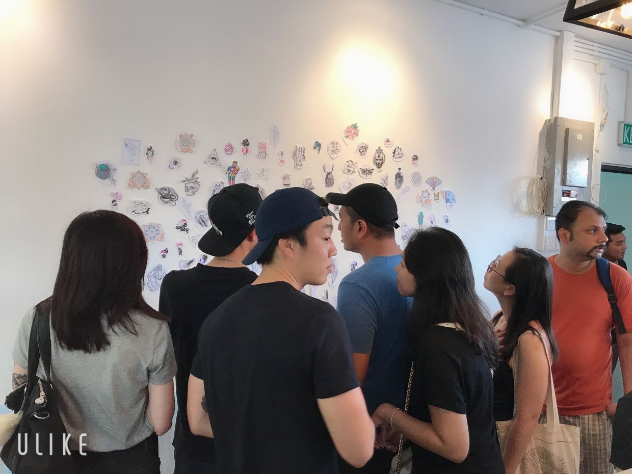 Tattoo flashes are designs drawn by tattoo artists, usually displayed on the walls of their studios to give clients an idea of the types of tattoos that they can do. Enthusiasts surveying the tattoo designs during the previous year's charity flash event. Photo: Alvin Chong