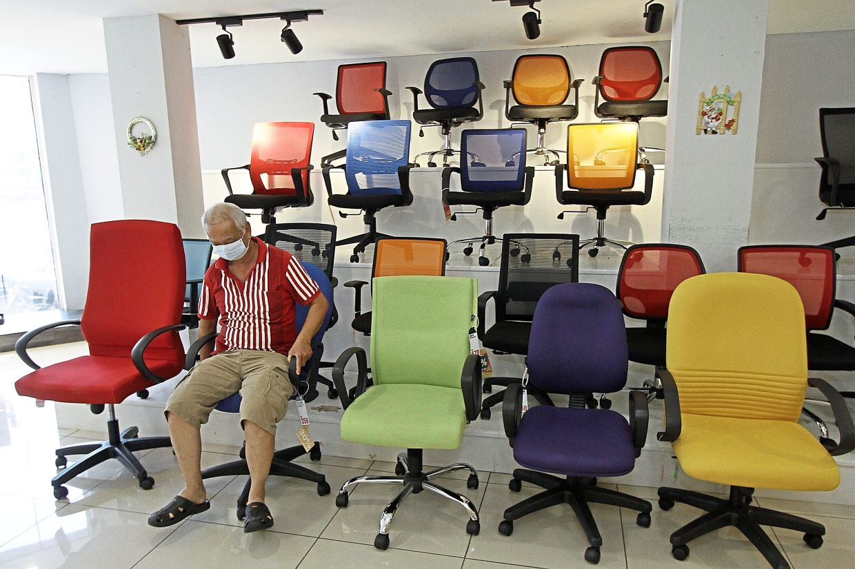 A customer trying out an office chair at a shop.