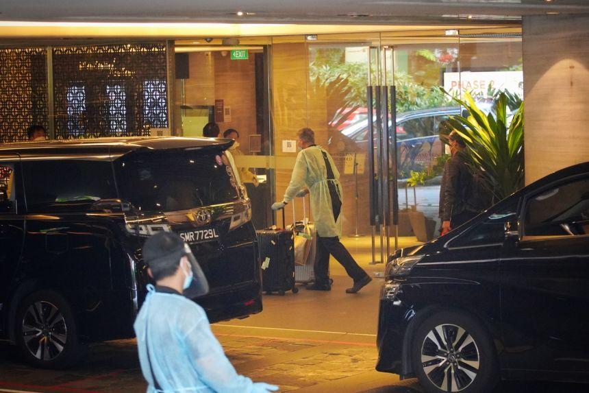 El personal con equipo de protección personal ayuda con el transporte de equipaje mientras los huéspedes abandonan el Mandarin Orchard el domingo (20 de diciembre de 2020).  Tee Straits Times / ANN