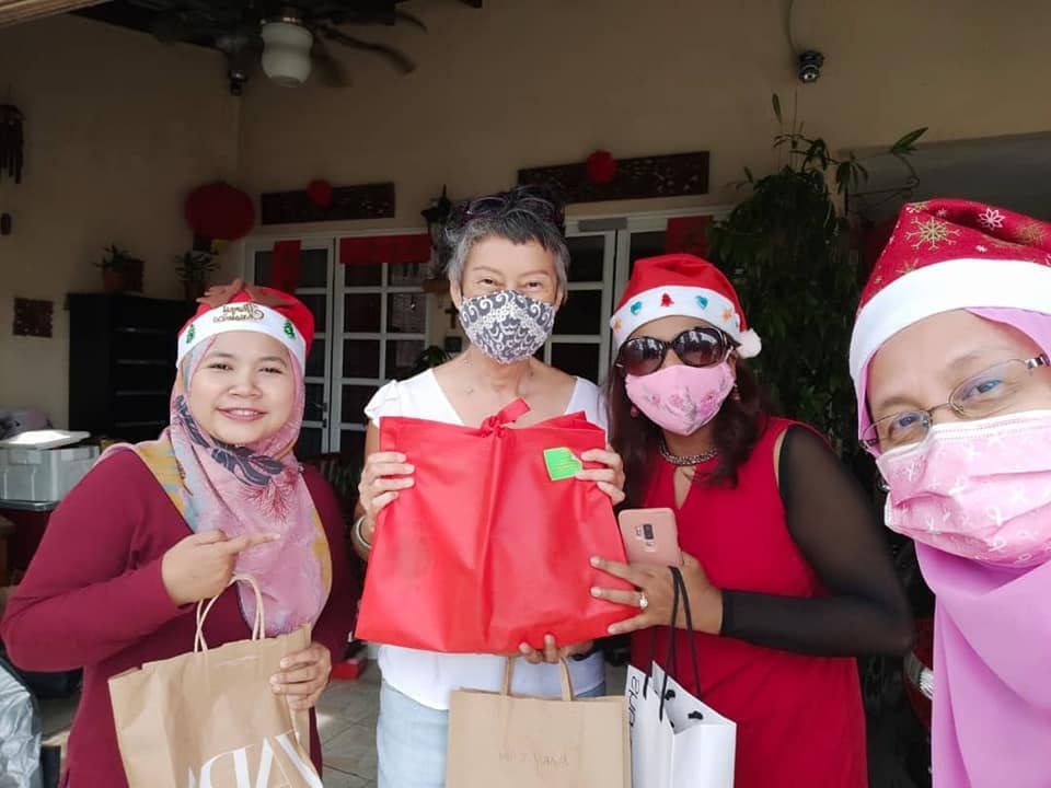 Pink Unity member Mary Chua (second from left) recceiving her party pack from Santa's helpers (fr left) Noorzailawati Sanuddin, Mahani Kassim and Mariana Hussein.