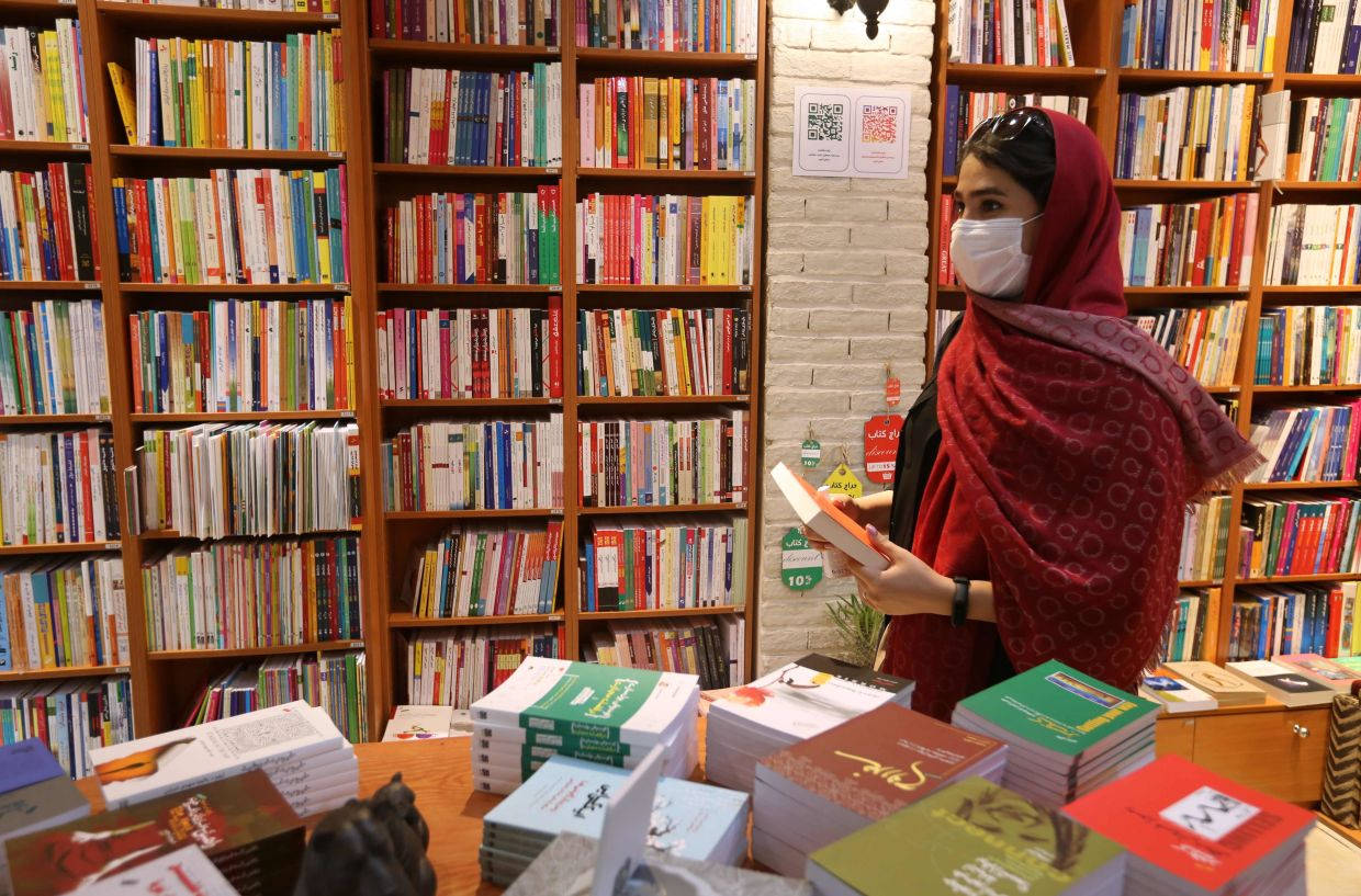 A woman picks a book at a bookstore on Enqelab (Revolution) street in Iran's capital Tehran. Photo: AFP