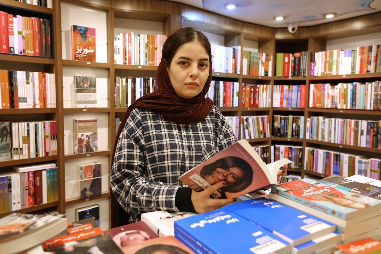 A bookshop worker Sepideh Daryan arranges the best-sellers at the Nashre-Cheshmeh Publishing House on Karim Khan street in Tehran. Photo: AFP