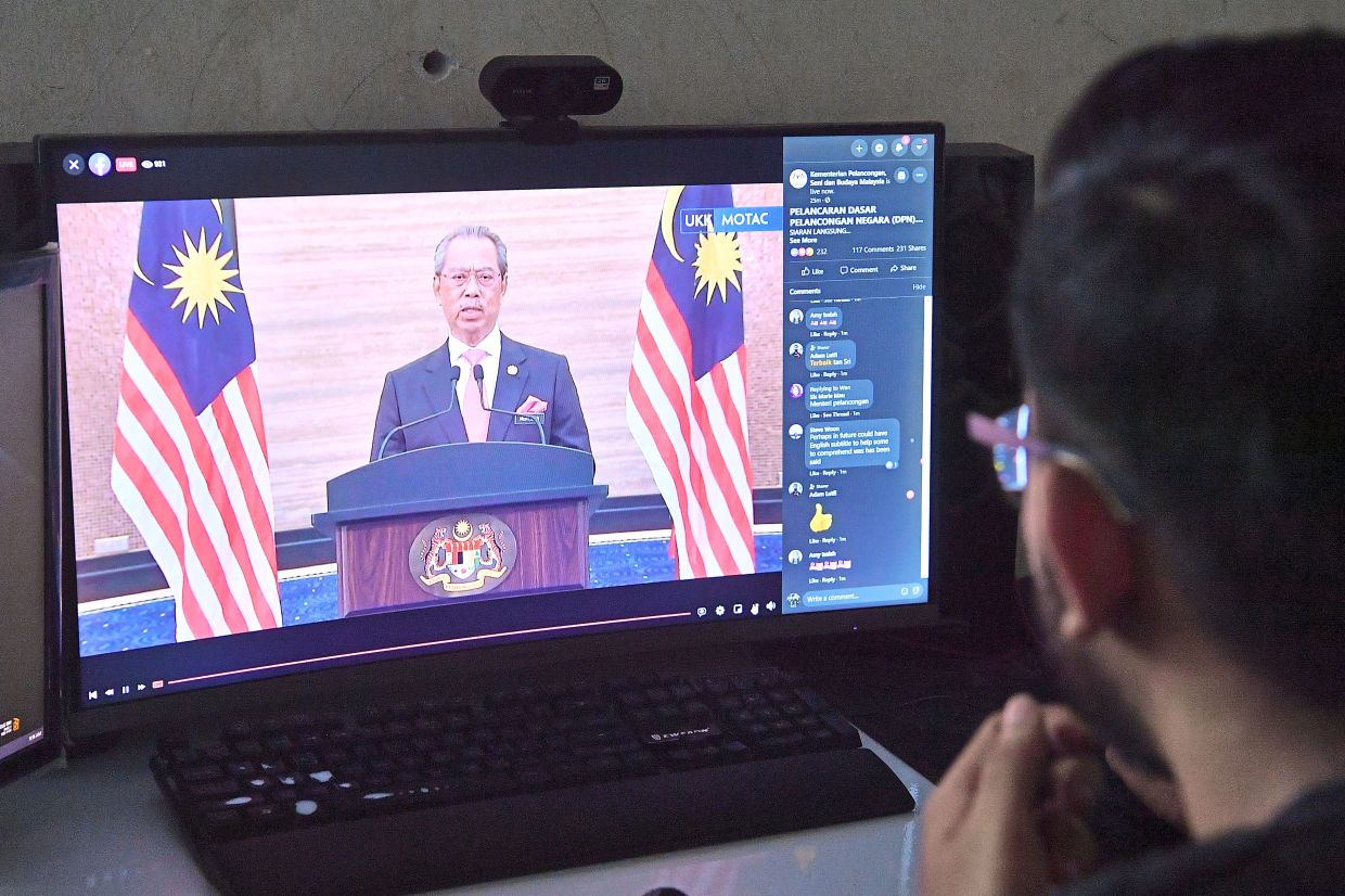 Important news: A man watching Muhyiddin's speech during the virtual launch of the National Tourism Policy 2020-2030. — Bernama