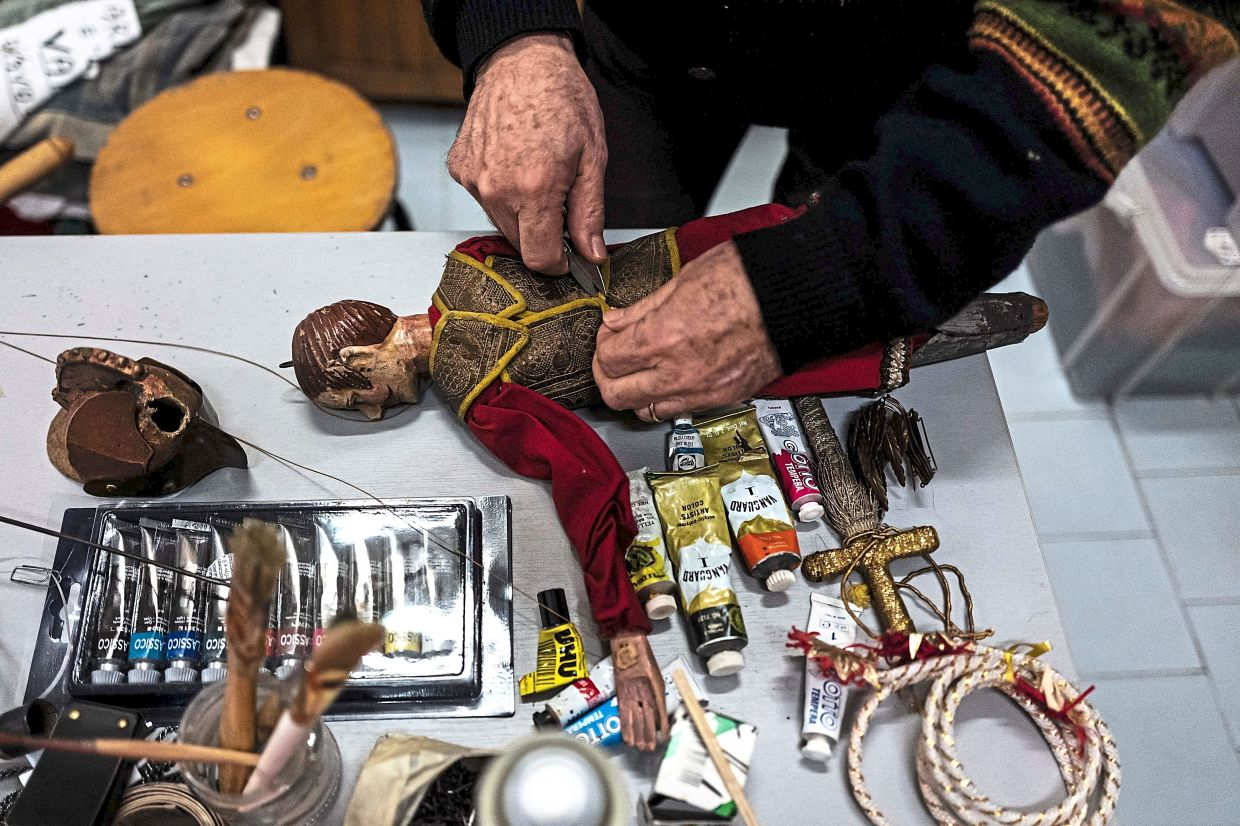 Grilli fixes dolls at the Alfa Theater lab in Turin.  Photo: AFP