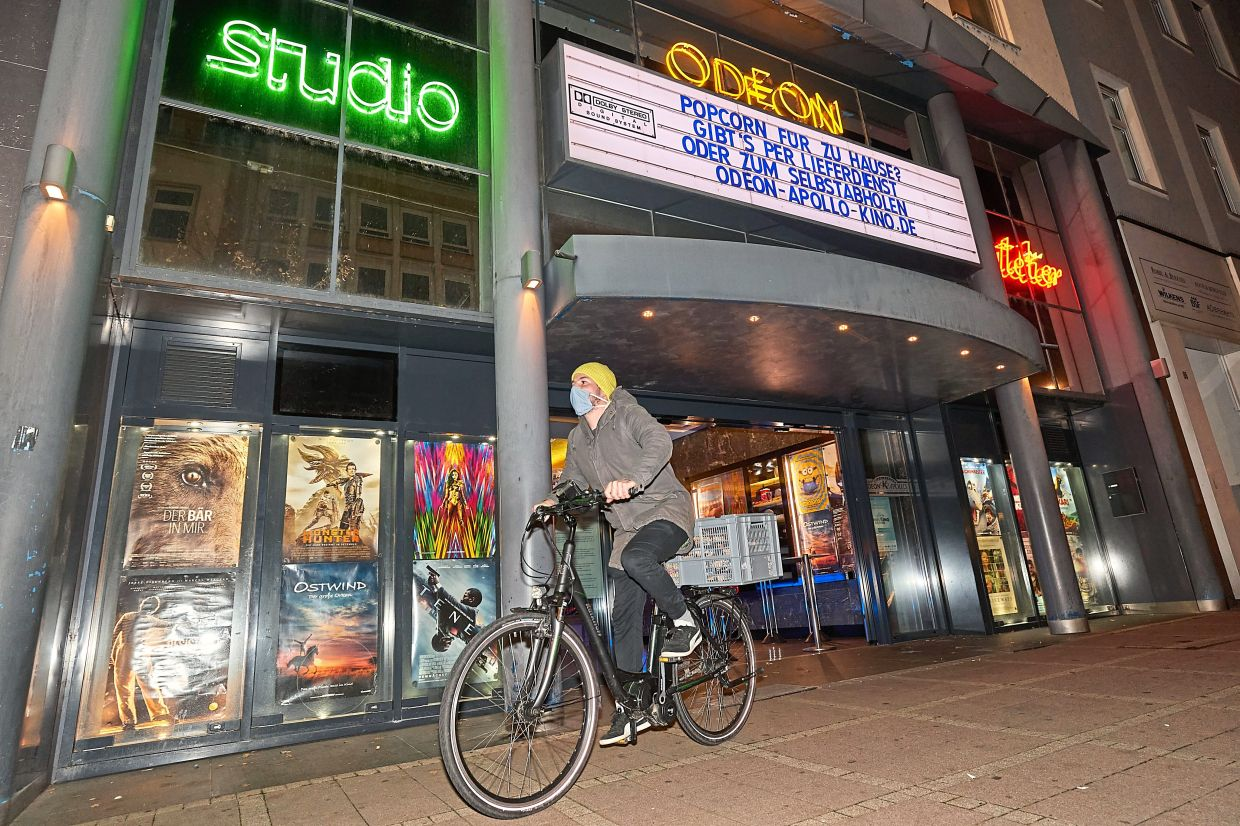 Yannic Koch rides an e-bike through the city of Koblenz at night to bring fresh popcorn from the Odeon Apollo Cinema to his customers.
