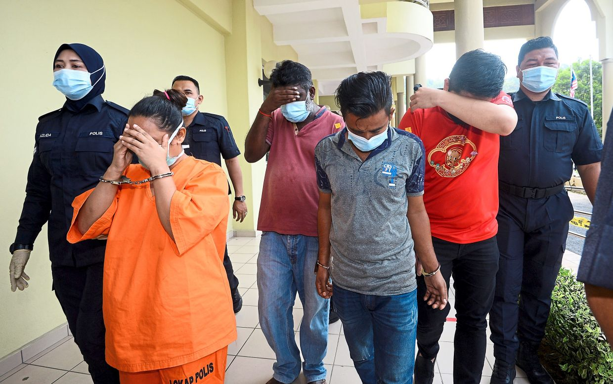 Police escorting the suspects of effluent dumping into Sungai Gong at the Sessions Court in Selayang on Nov 11. — Filepic