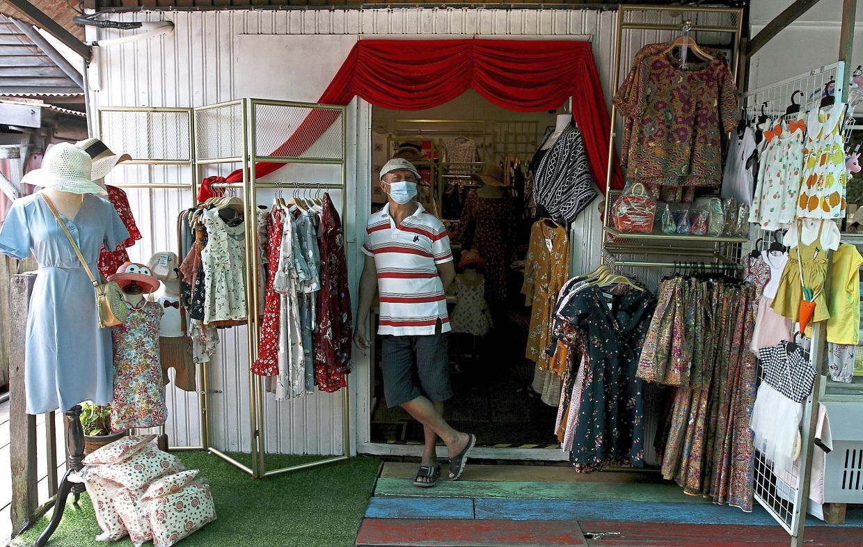 Chew waiting for customers at his clothing and souvenir store at Chew Jetty.