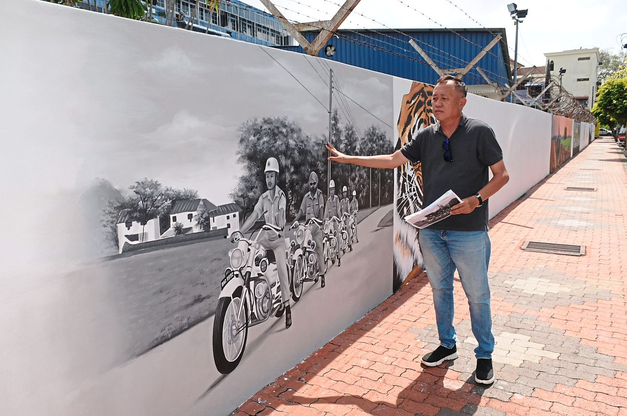 Chen showing his mural of police officers riding their motorcycles.