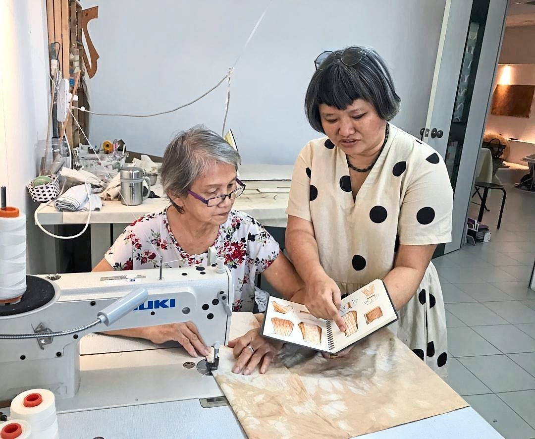 Wong explaining a design to her mother, Chu Yok, who is responsible for sewing all their products.