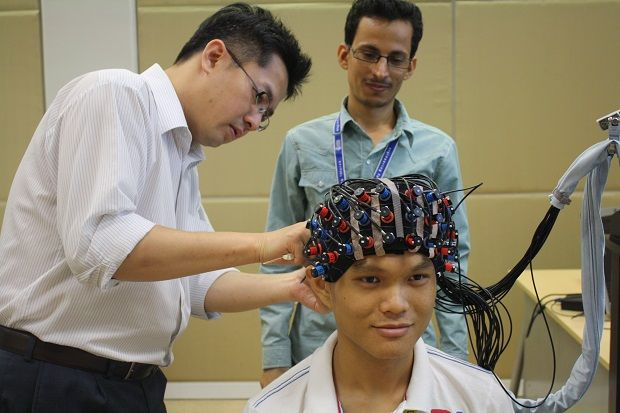 Tang conducting assessment and intervention on a participant using the functional near-infrared spectroscopy (fNIRS) to address stress at work to achieve optimum performance.
