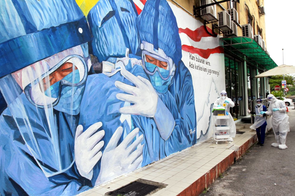 Medical personnel on standby for motorists at a drive-through Covid-19 screening facility at Klinik Ajwa in Shah Alam, in front of a mural paying them tribute. — KK SHAM/ The Star