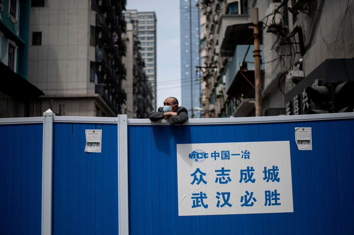 A man wearing a face mask looks over a barricade set up to keep people out of a residential compound in Wuhan in China's central Hubei province on April 14. -- NOEL CELIS/ AFP