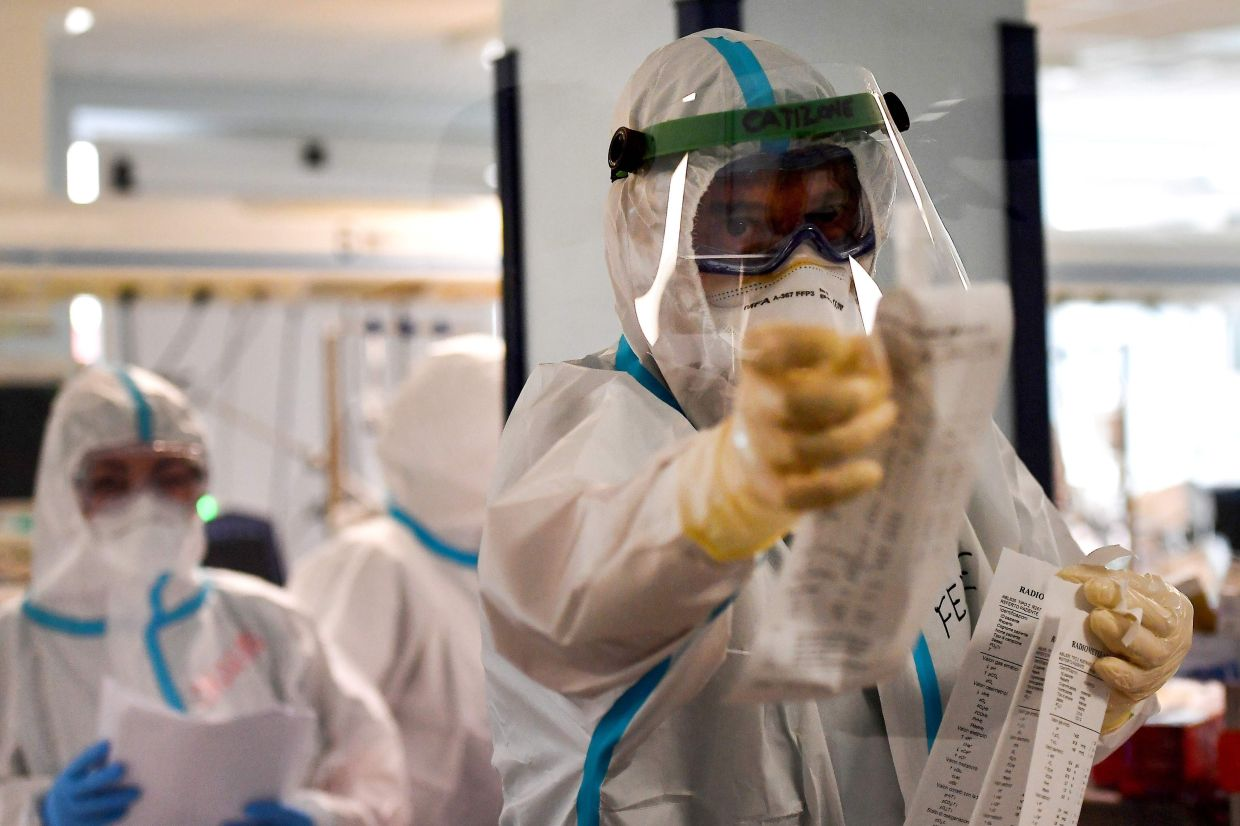Medical staff wearing personal protective equipment work in the Intensive Care Unit for Covid-19 cases in the San Filippo Neri hospital in Rome, in October. -- TIZIANA FABI/ AFP)