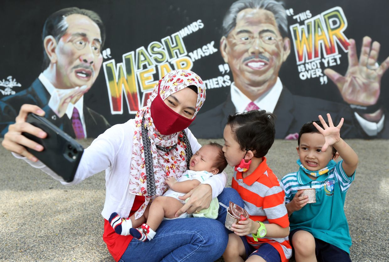 Azza Azrin Juri (left), 33, taking a wefie with her children (from left) one-month-old baby boy Arreza Izzayne, Arrizqy Izzran, 6, and Arruzain Izzul, 4, near the mural of Muhyiddin and Dr Noor Hisham in Shah Alam. — IZZRAFIQ ALIAS/ The Star