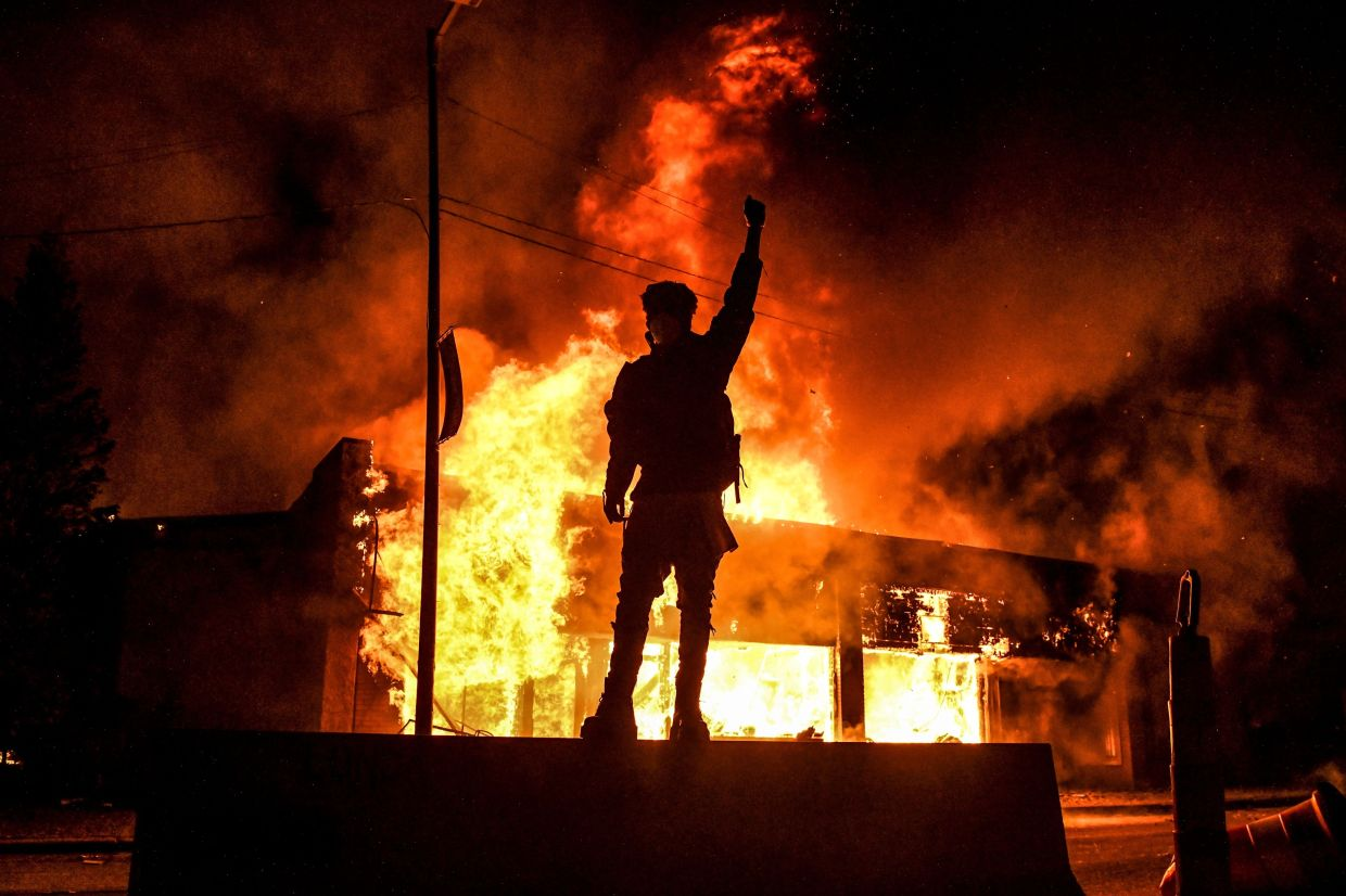 A protester reacts standing in front of a burning building set on fire during a demonstration in Minneapolis, Minnesota, on May 29, 2020, over the death of George Floyd, a black man who died after a white policeman kneeled on his neck for several minutes. -- CHANDAN KHANNA/ AFP