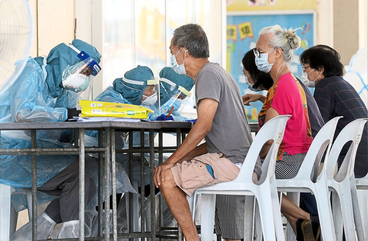 Healthcare workers taking down details of residents before the  Covid-19 test at SJK (C) Chen Moh in Petaling Jaya Old Town after  certain areas were placed under enhanced MCO. — Filepic