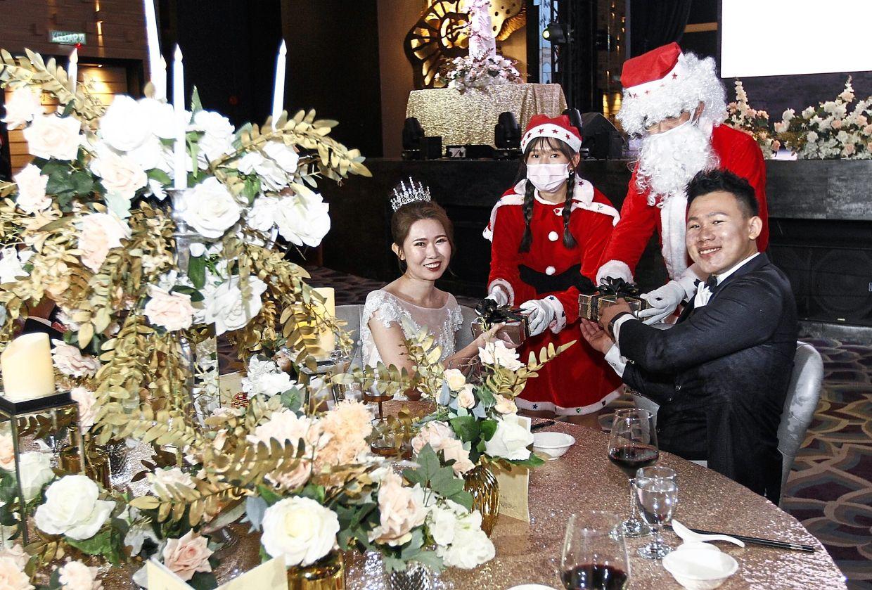 Santa Claus and a Santarina giving presents to bride Ang Shy Yin and bridegroom Ooi.