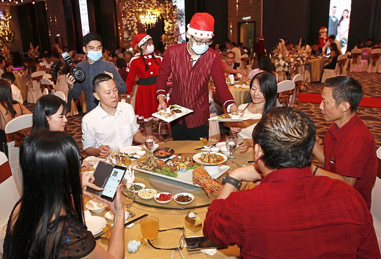 A hotel staff member wearing a Santa hat serving the guests at the  wedding dinner.