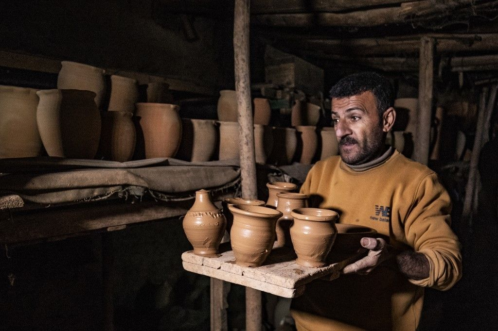 Petros' son carrying vases for drying at his father's workshop.
