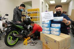 Motorcycle repair shop owner giving away face masks