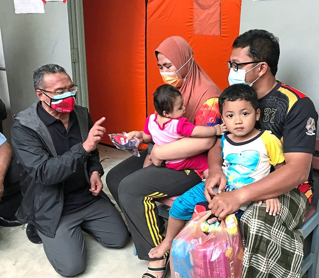 Families in need receive some comfort: Hishammuddin (left) handing out masks and food items to teacher Abdul Aziz and his wife Khairiyatul who were seeking relief at the SMK Seri Sembrong temporary flood shelter in Kluang.