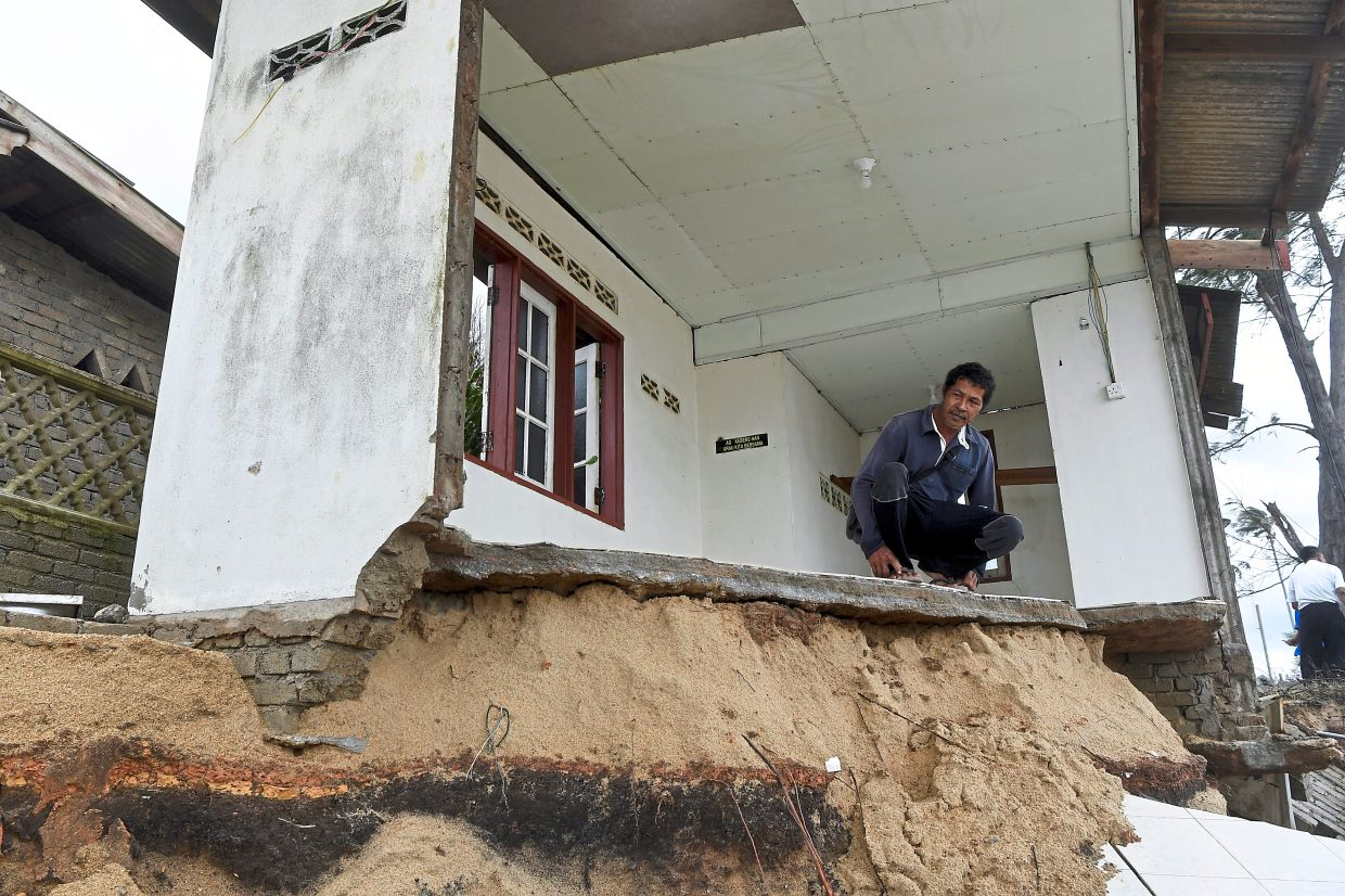 Mohd Zaki Mustafa, 66, surveying the corrosion damage at a surau following a high tide phenomenon at Kampung Pengkalan Maras, Terengganu. —Bernama