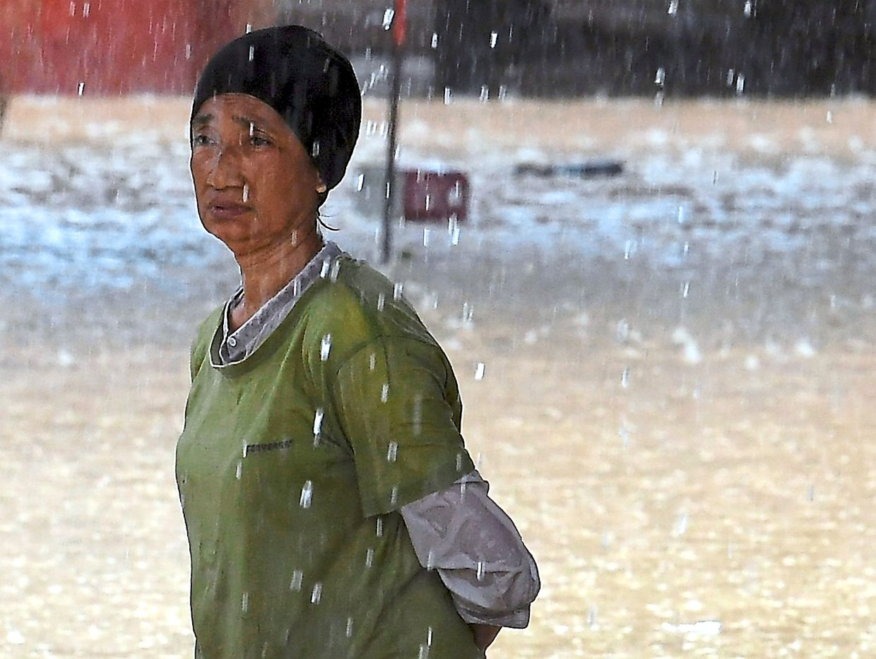 Water woes: A woman looking forlorn after her home was hit by floods in Kampung Galing, Pahang. — Bernama