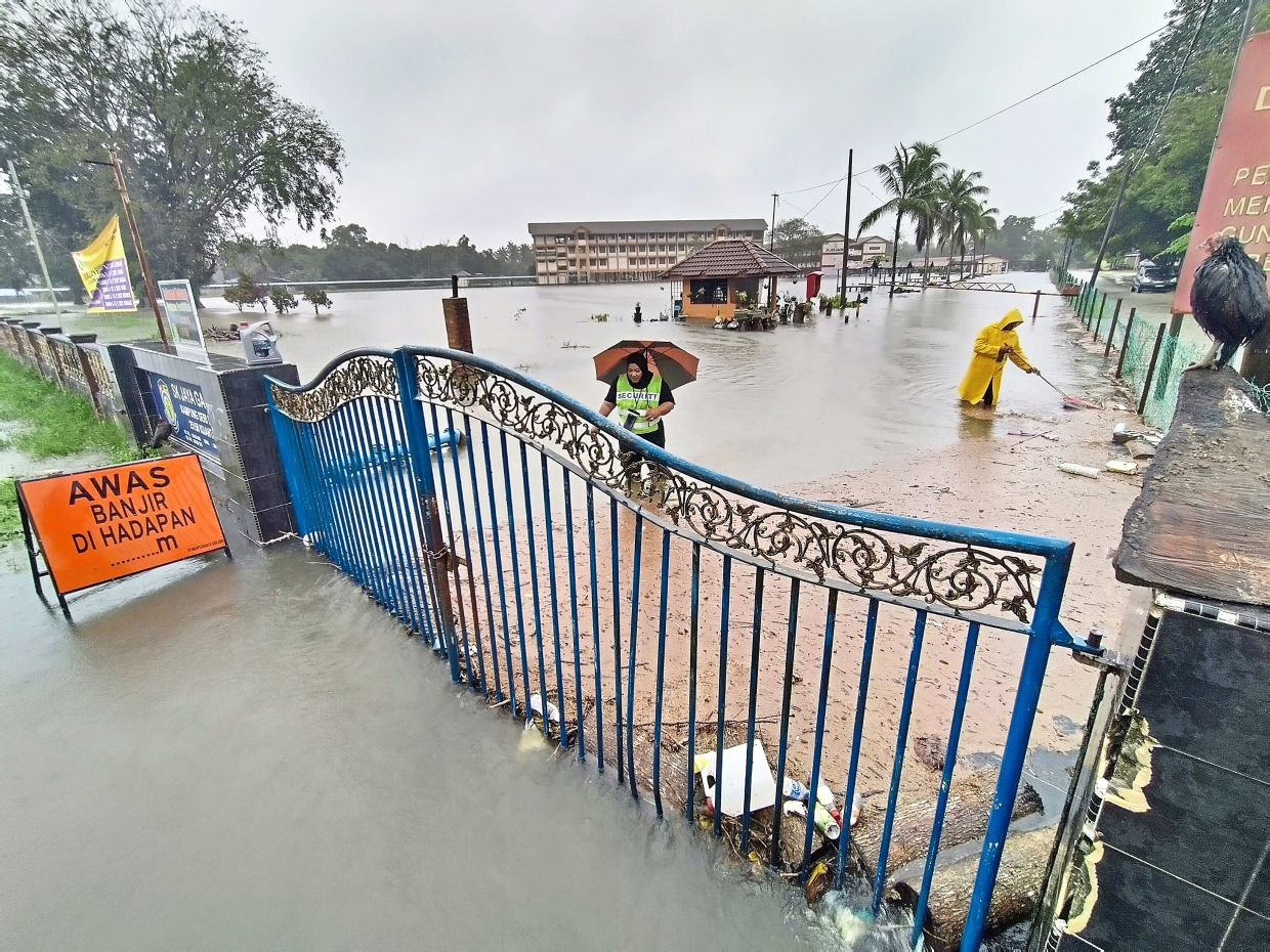 In deep water: People clearing tree branches and debris stuck at the entrance of SK Jaya Gading in Kuantan. — AZMAN GHANI/The Star