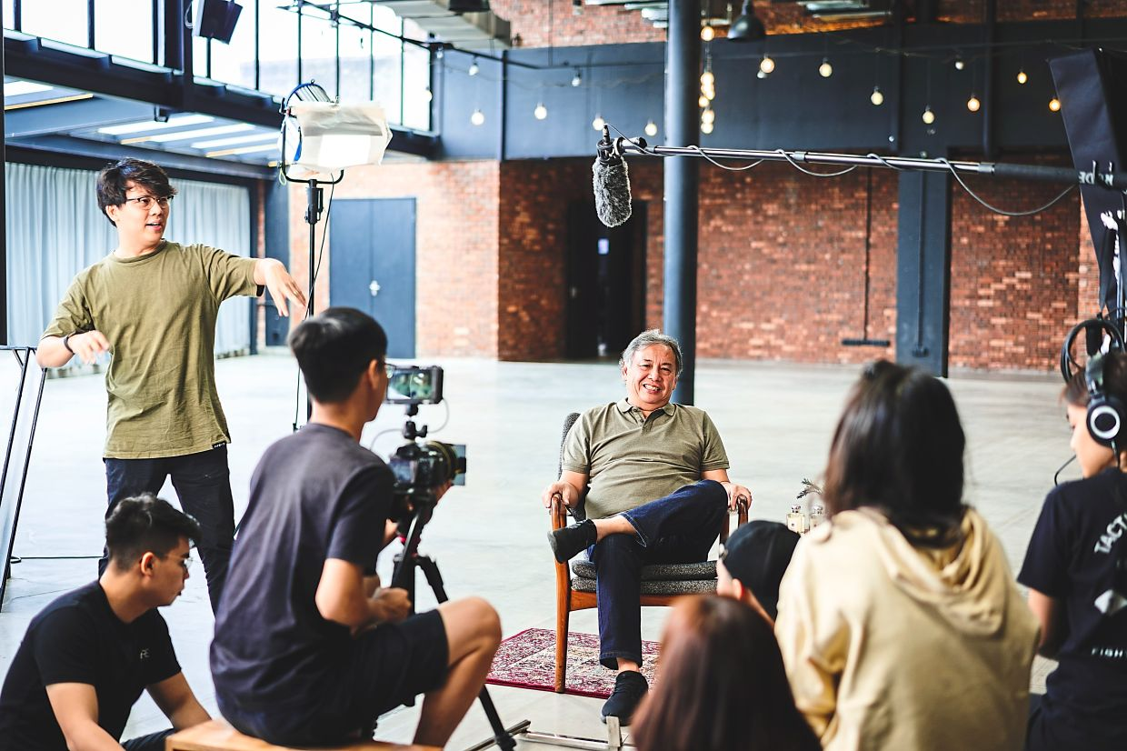 Ho (standing) at a video shoot in June 2019, reveals that most of their earnings come from doing branded videos which feature products or services sponsored into them, rather than YouTube directly. — Core Studios