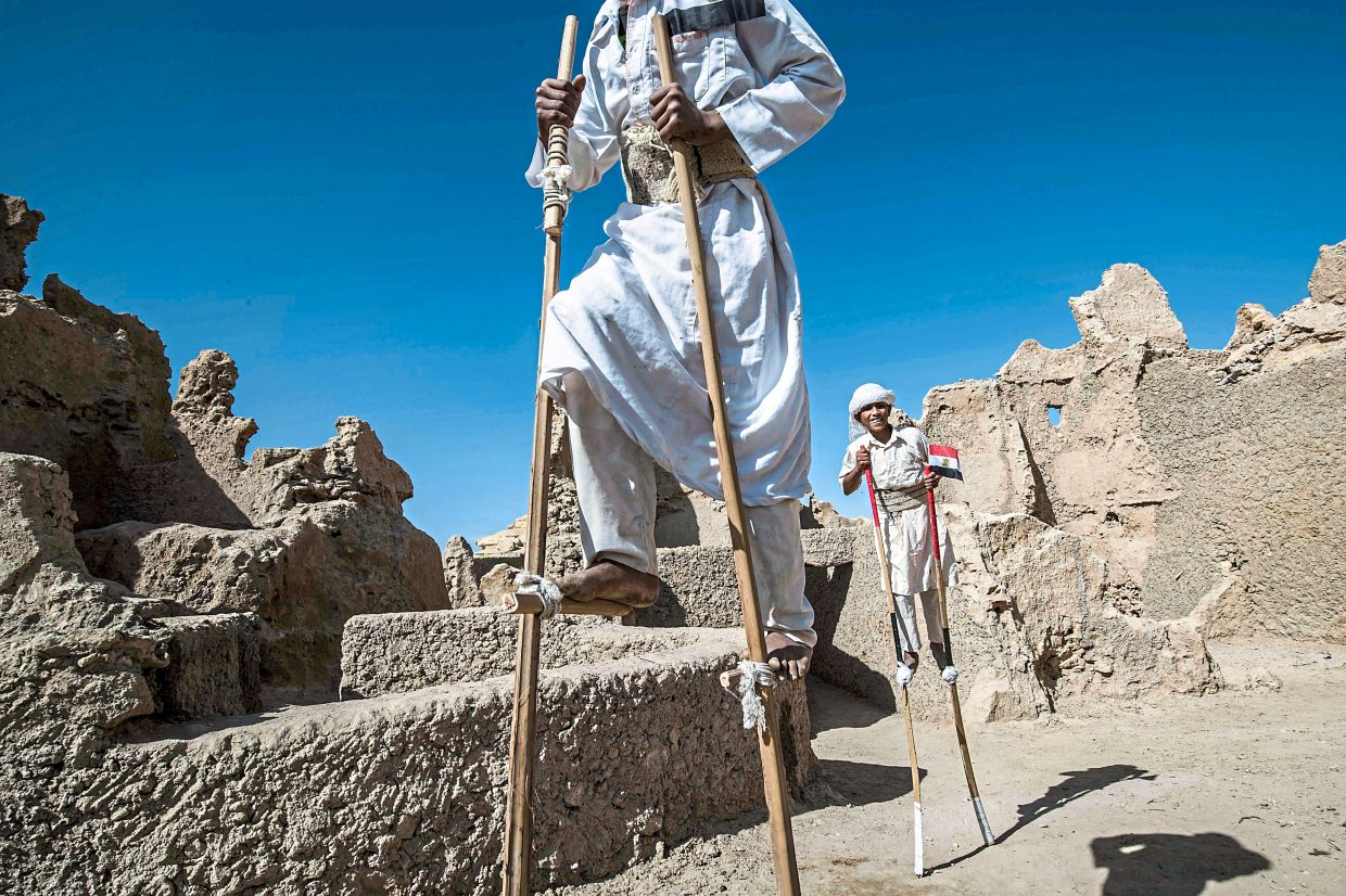 Egyptian school children dressed in traditional outfits walking on stilts during a recent celebration to mark the inauguration of the fortress of Shali.