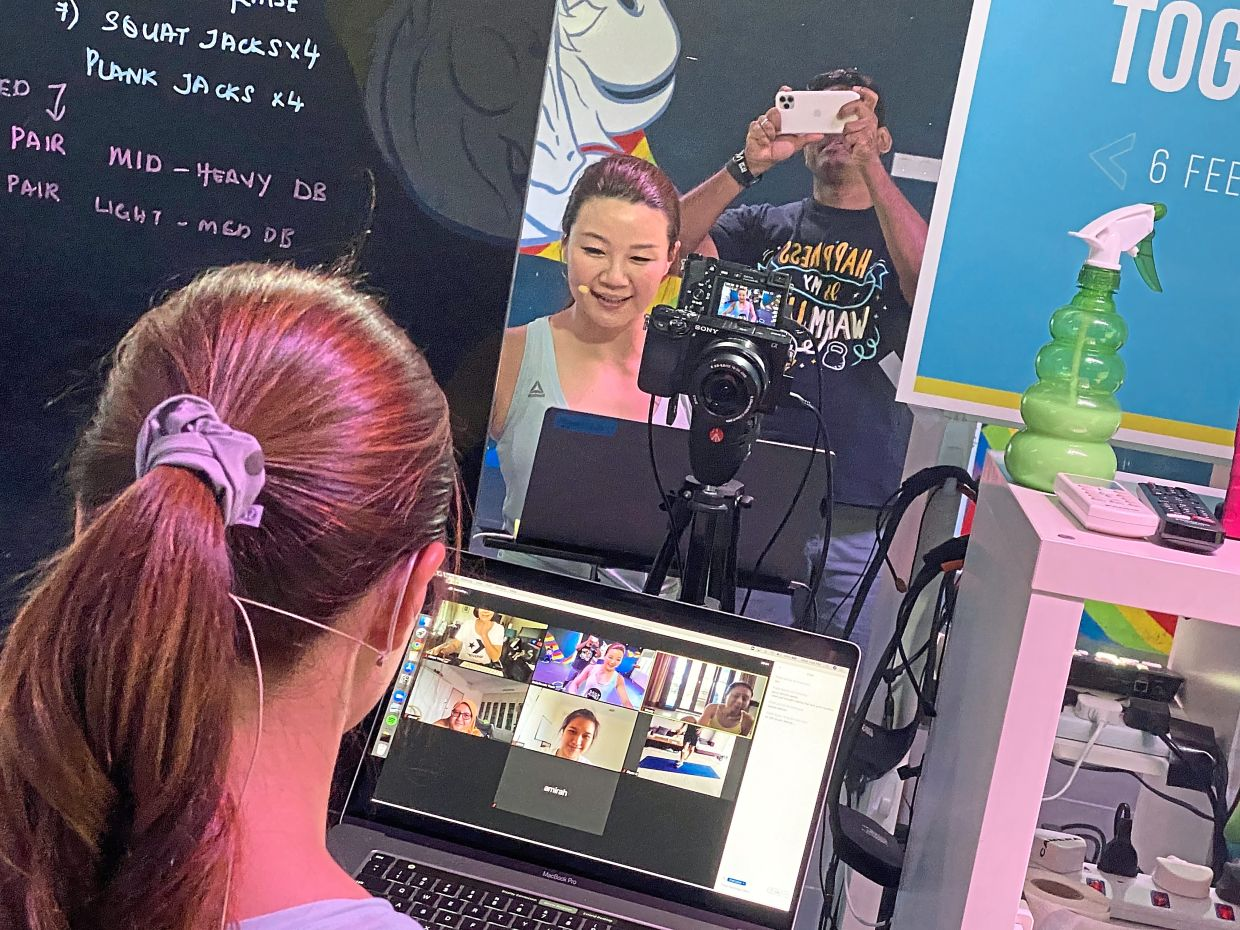 DailyMuscle gym co-founders Kimbeley Yap (left) and Noel livestreaming one of their daily classes for members.