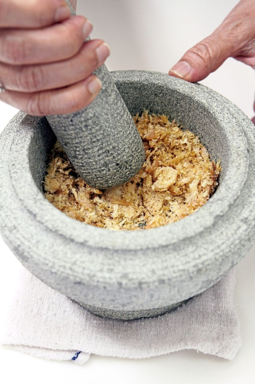 Pound the dried shrimp in a mortar and pestle until it becomes floss-like.