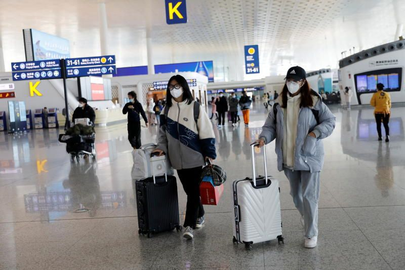 Travellers walking with their luggage at Wuhan Tianhe International Airport. - Reuters