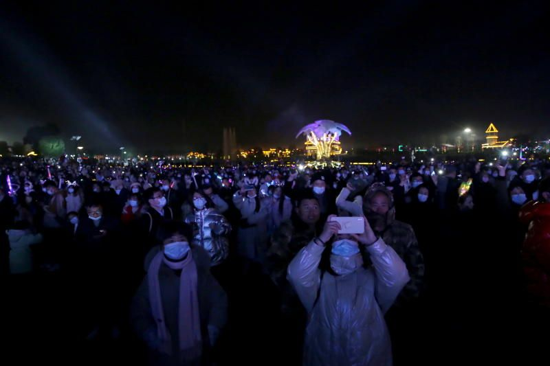 People wearing face masks attending a celebration event on New Year's Day at a park in Wuhan. - Reuters